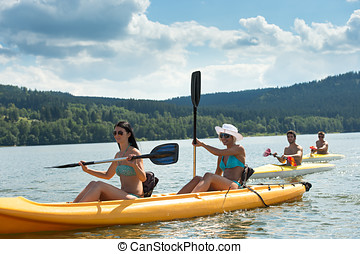 Young students kayaking in the sunshine - Young women rowing...