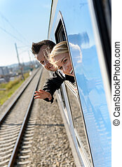 Woman man heads out the train window smiling travel...
