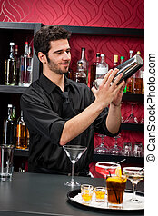 Young bartender make cocktail shaking drinks - Handsome...