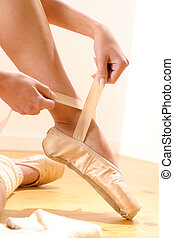 Ballet dancer tying slippers around her ankle woman...