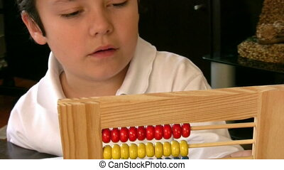 Six years old boy with abacus - Little schoolboy sitting at...