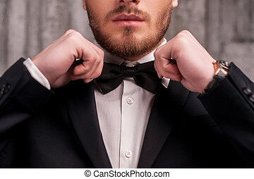 Tying a bow tie. Cropped image of handsome young beard man...