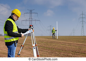 Geodesist measure land on construction site - Land surveyors...