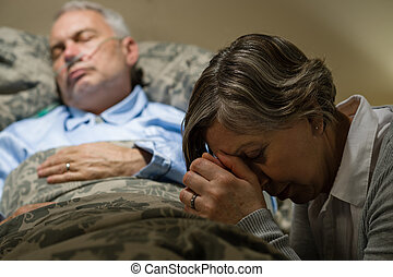 Uneasy senior woman praying for sick man - Senior woman...