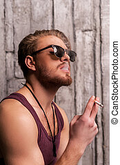 Cool handsome smoking. Side view of handsome young man in...