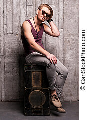 Cool and handsome. Handsome young man in sunglasses sitting on the music speaker and holding hand in hair