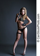 Cute young go-go dancer posing on gray background - Cute...