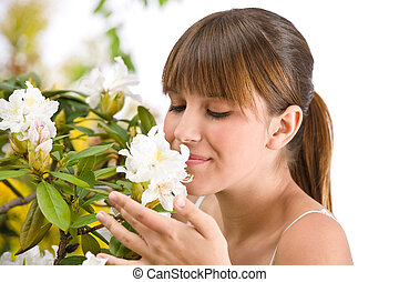 Portrait of woman smelling blossom of Rhododendron flower on...