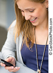 Smiling woman reading text message on cellphone - Smiling...