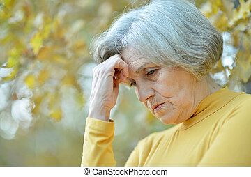 Handsome elderly woman walking outdoors in autumn