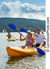 Smiling couple rowing kayak sunshine - Young friends...