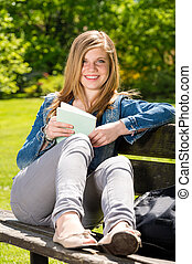 Young female student studying in the park sitting on bench