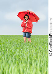 Elated teenage girl holding red umbrella on meadow