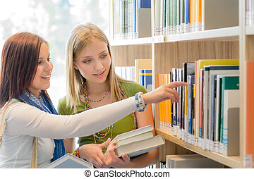 High school library happy student search book - Two female...
