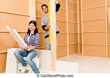 Home improvement young couple with blueprints - Home...