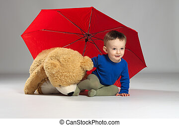 Young boy toddler - Toddler boy sitting under a red umbrella...