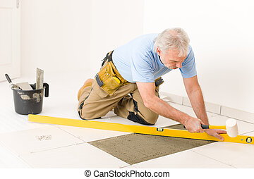 Home improvement, renovation - handyman laying ceramic tile...