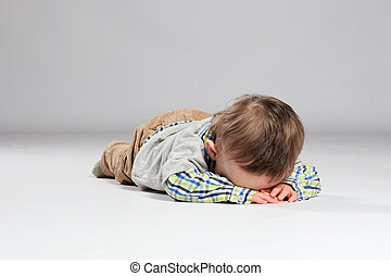 Young boy toddler - Tired toddler boy lying on the ground...