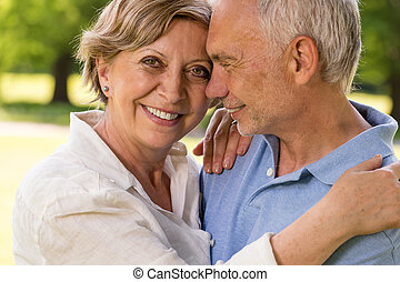 Elderly wife and husband cuddling outdoors - Elderly wife...