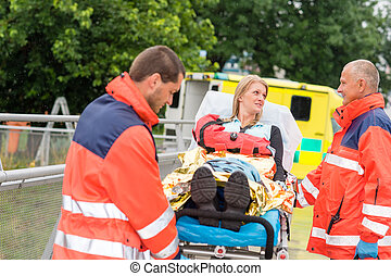 Injured woman talking with paramedics emergency