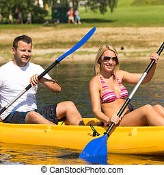 Couple sitting in kayak on a sunny day - Young couple...