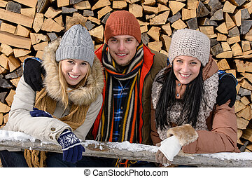 Young people in winter clothes posing outside