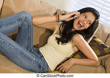 Happy Phonecall - A beautiful young Hispanic woman laying on...