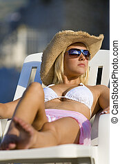 Sun Bathing - A beautiful young blond woman in sunglasses...