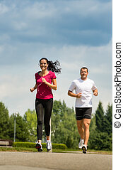Couple friends running a race in park - Playful couple...