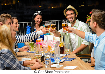 Group of young friends drinking beer outdoors terrace night...