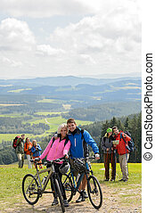 Posing cyclist couple on mountain with bikes - Posing...