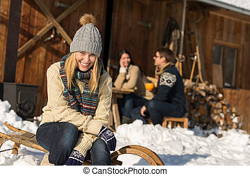 Young woman with friends snow winter cottage - Young woman...