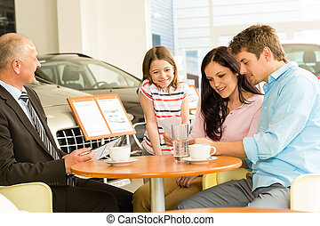 Couple reading papers in car dealership - Young couple...