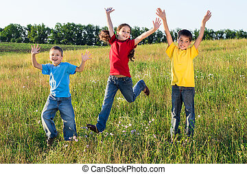 Jumping kids on green field - Happy jumping kids on green...