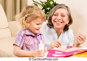 Little girl with grandmother play glue paper - Grandmother...