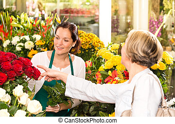 Senior customer buying red roses flower shop florist women...