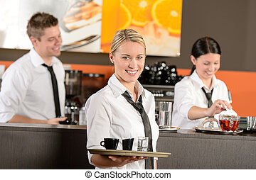 Confident waitress serving coffee with tray colleagues...
