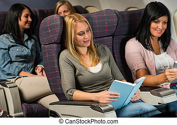 Young woman passenger read book airplane flight - Leisure...