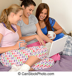 Three cheerful girls surfing on the net on laptop