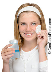 Cheerful smiling girl removing cleaning make-up face lotion