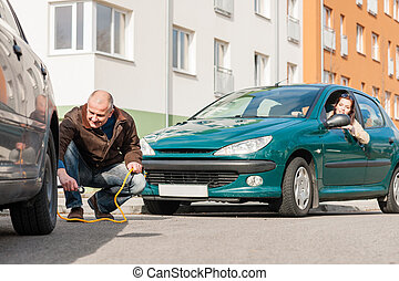 Mature man helping woman with her car
