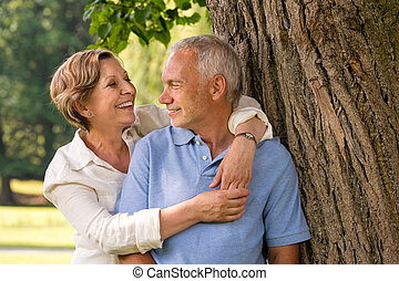 Happy pensioner couple cuddling outdoors