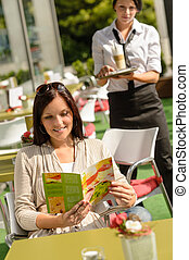 Woman checking menu waitress bringing order coffee cafe bar...