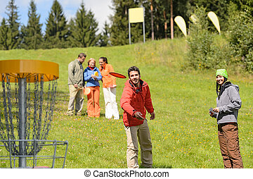 Couple throwing frisbee disc at springtime park - Couple...