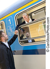 Woman leaving with train man farewell couple smiling travel...