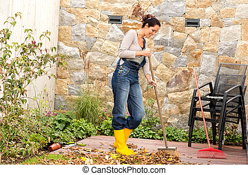 Young woman sweeping leaves veranda backyard happy - Young...