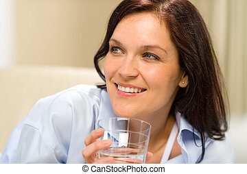 Smiling brunette woman with glass of water