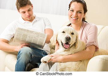 Resting joyful couple sitting and petting dog man reading...