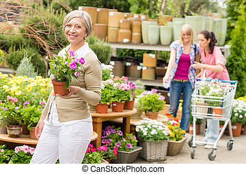 Garden center senior lady hold potted flower - Senior lady...