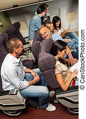 Leisure travel people enjoy flight airplane cabin talking...